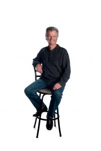 Garth Roberts, in sweater sitting on a chair